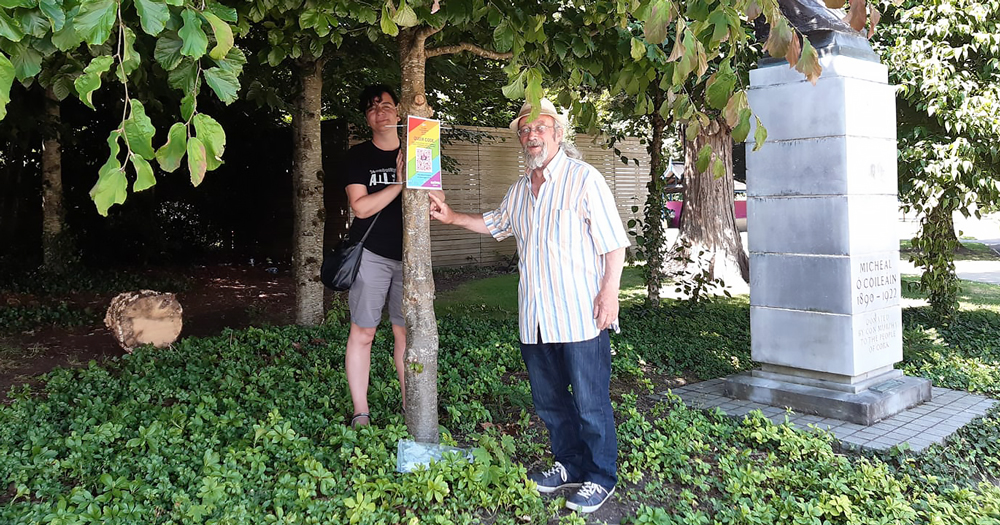 Two people hanging a rainbow coloured sign on a tree in a park