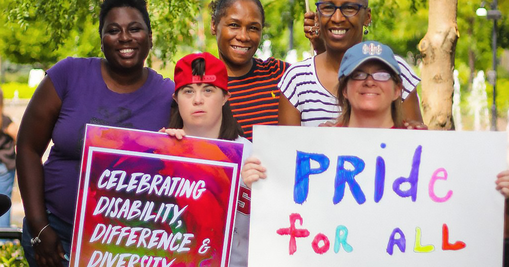 a group of 5 people smiling to the camera, are holding signs for disability pride month