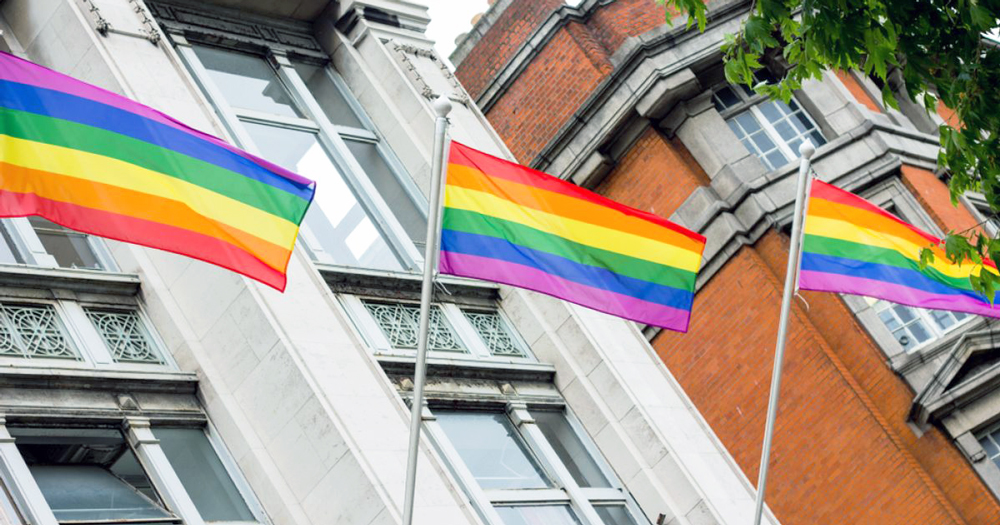 Rainbow flags on poles outside a huge building