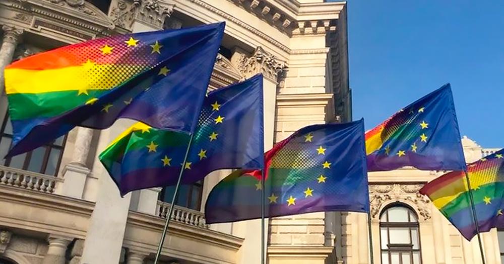 The EU flag and a rainbow flag flying outside a building