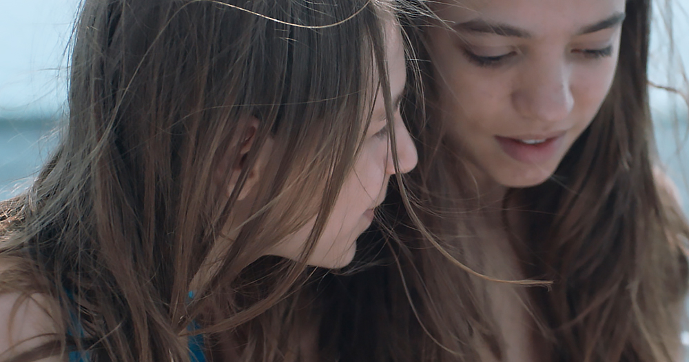 Two young women with long hair at the beach