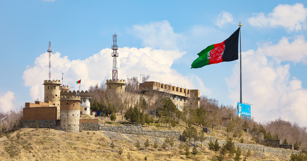 The Afghanistan flag flies in the foreground, a fortress can be seen in the background