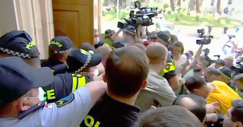 A mass of people clashing with police in the doorway of a building