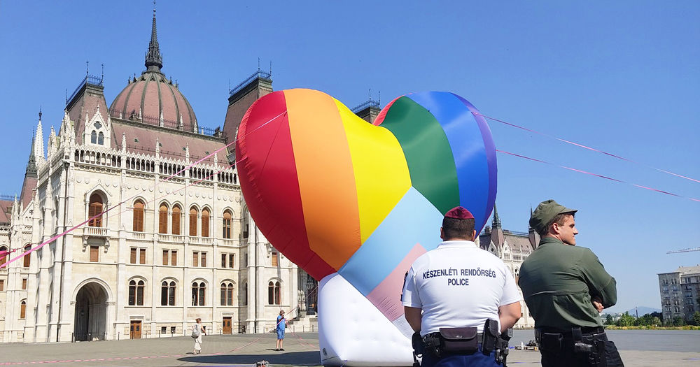 An inflatable rainbow coloured balloon outside an Eastern European building