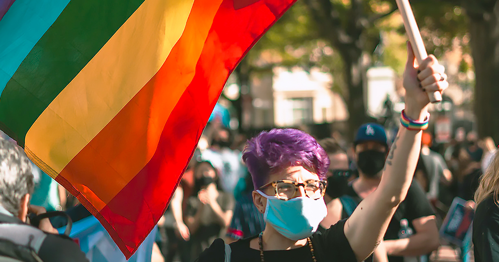A person in a facemask holding a rainbow flag