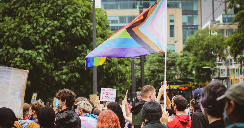 A group of people holding the rainbow flag