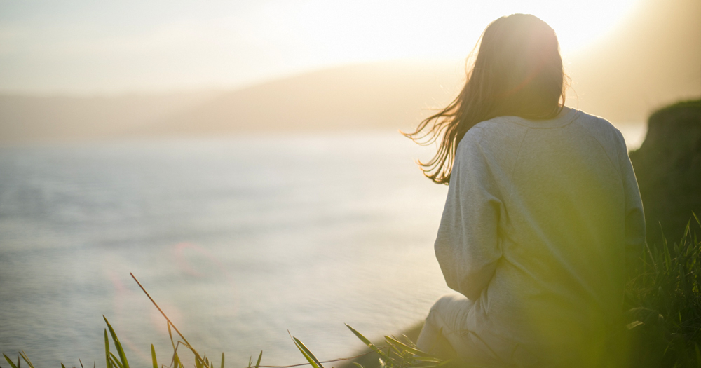 Woman sitting on a cliff looking at the sea. In this article, Louise Blake opens up about being pansexual