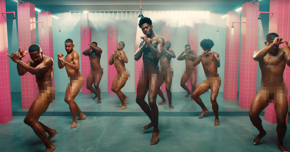 Lil Nas X dancing surrounded by naked man on the set of Industry Baby