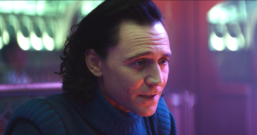 A long haired man in a futuristic diner