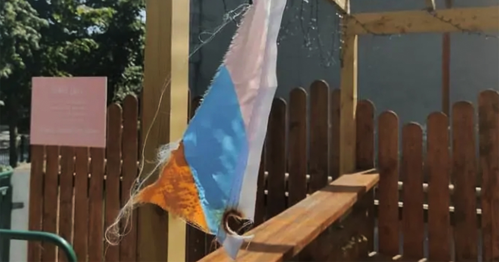 A torn and destroyed flag hanging from a wooden frame