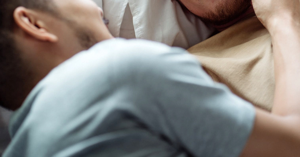 Two men embracing in bed