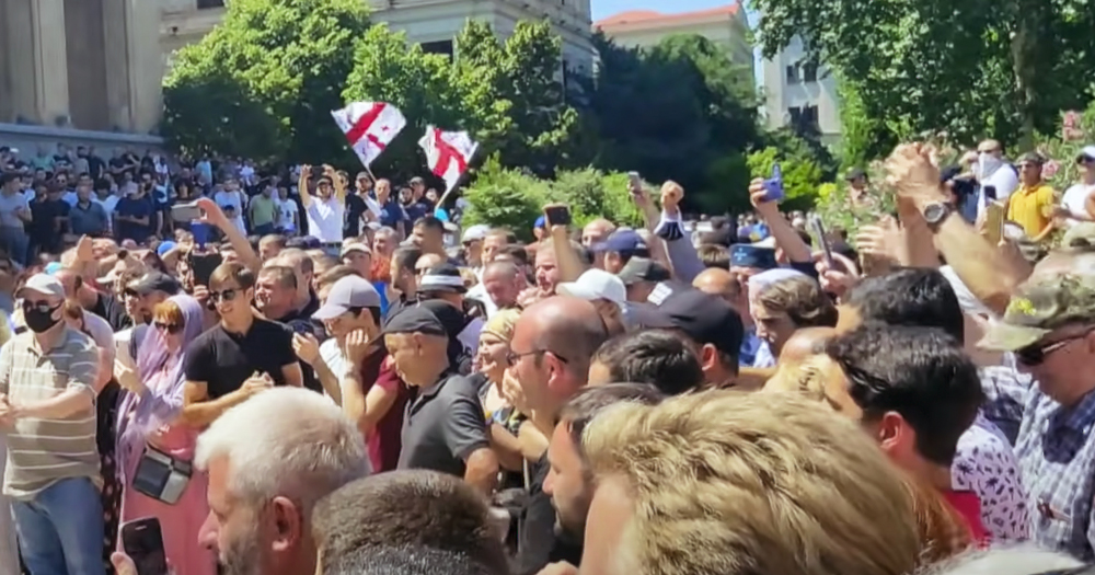 A mob of angry people waving Georgian flags