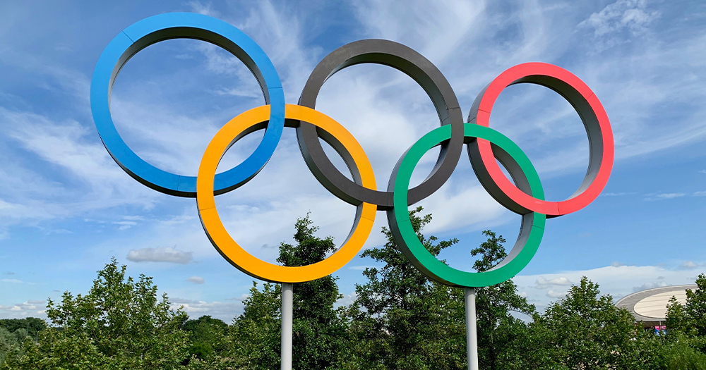 The five intersecting Olympic rings with the sky in the background