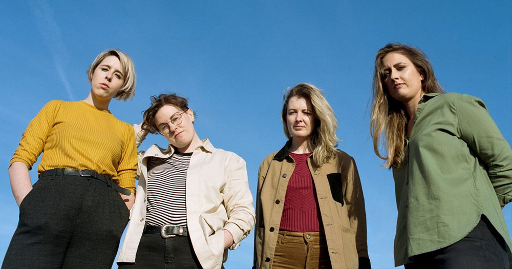 Four women standing with only the sky behind them