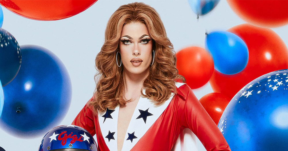 A drag artist with a long flowing wig and race car driver costume with balloons falling behind them
