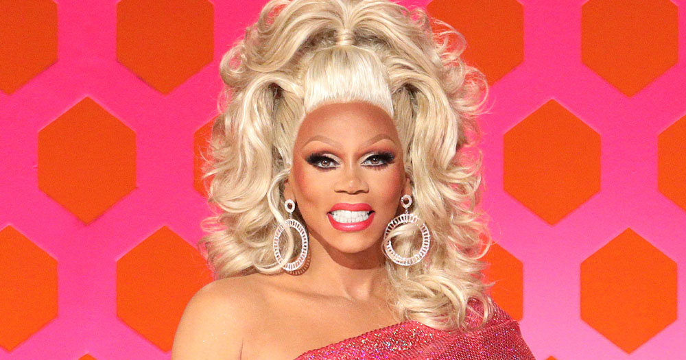 A smiling drag queen with a huge blonde wig