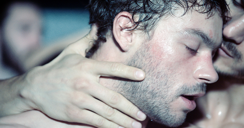 Two sweaty topless men embracing