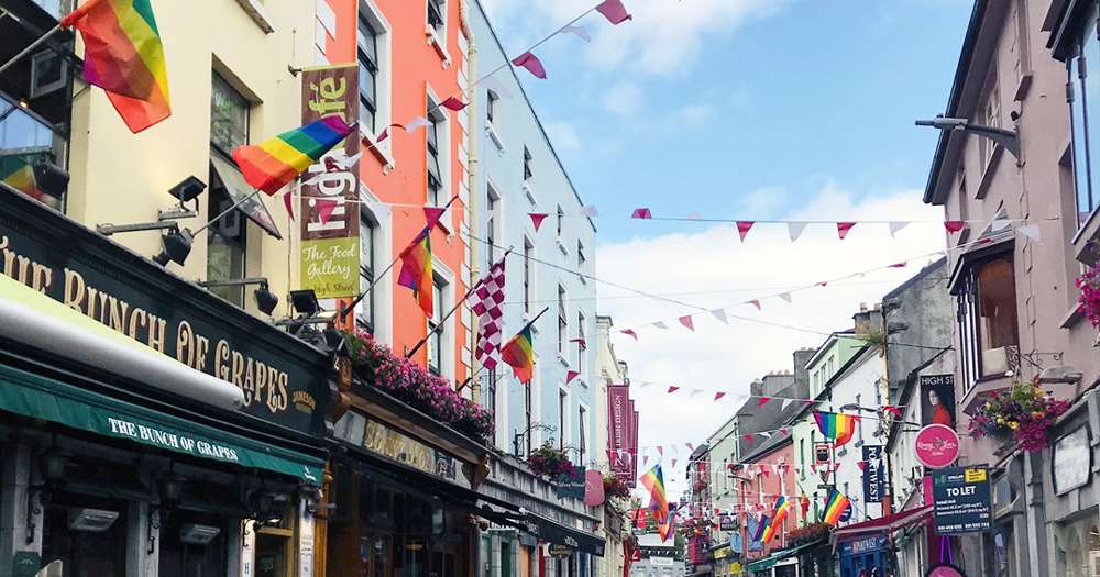 Rainbow streamers running from shop to shop on a city street
