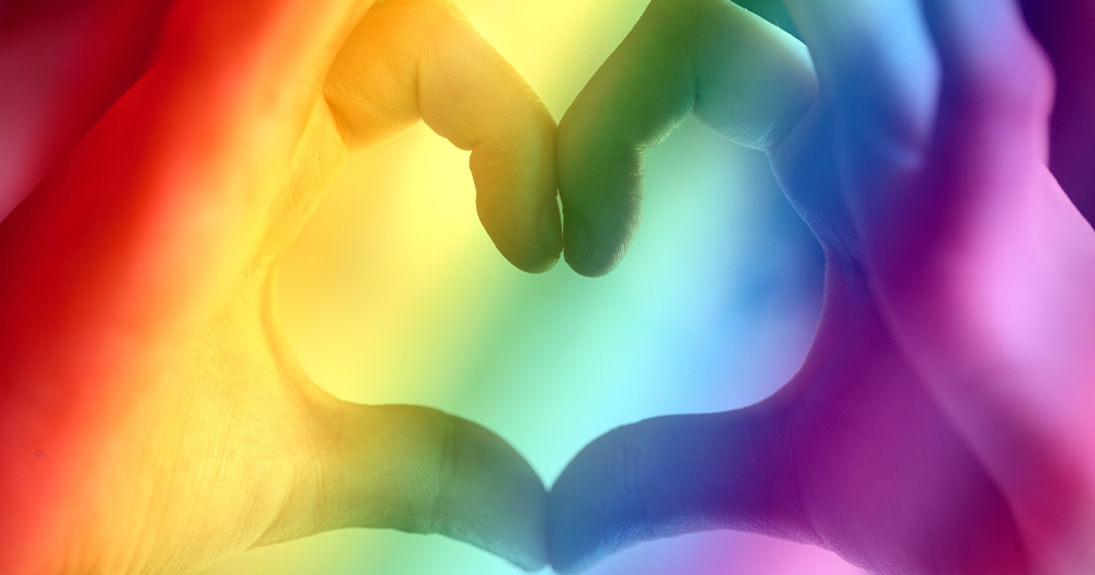 Hands forming a heart shape with rainbow colours overlaid