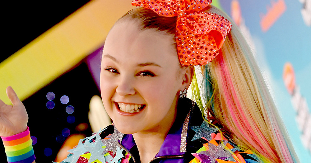 Jojo Siwa, who has been cast on Dancing With the Stars, is pictured smiling with a bright orange bow in her hair.