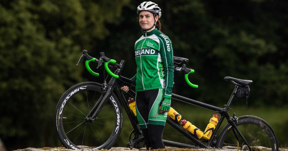 A woman in cycling gear standing beside a bike
