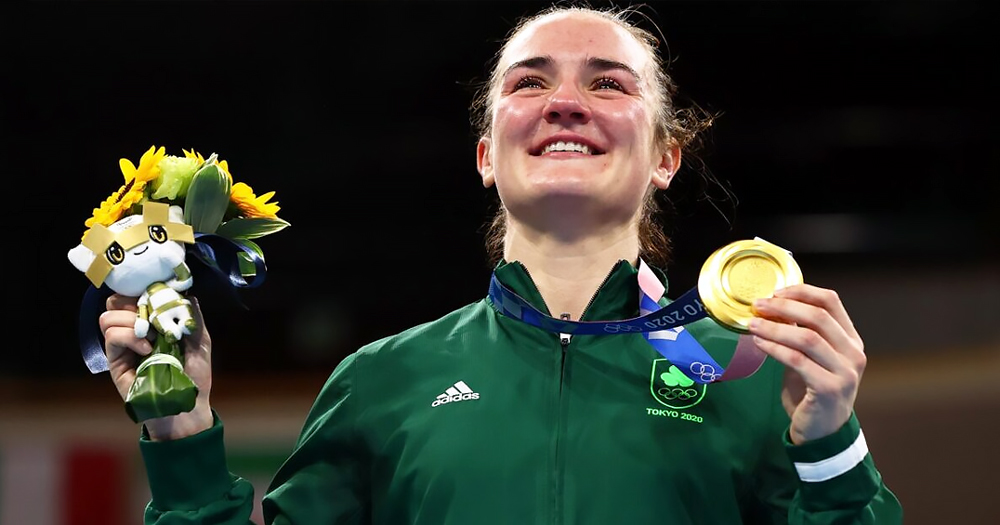 A smiling sportswoman holding a gold medal