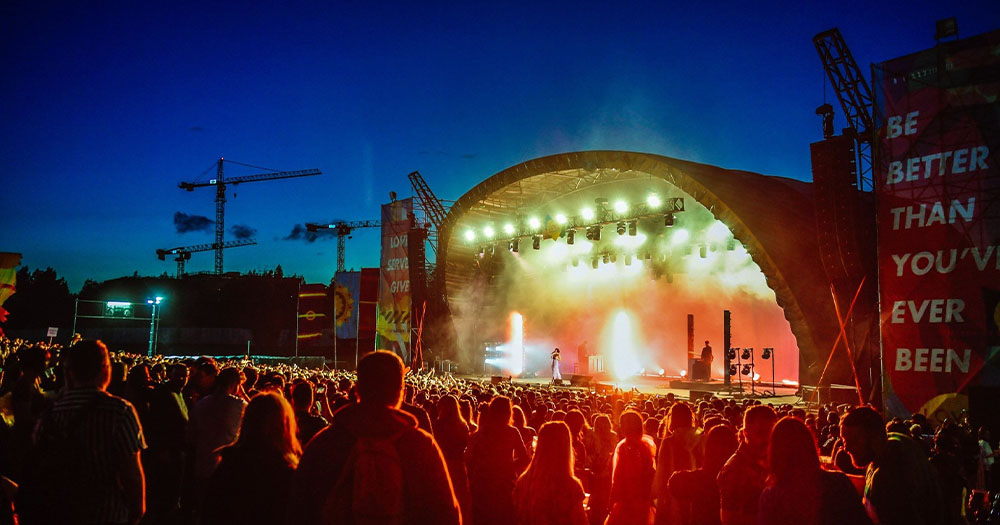 Thousands of people watching a festival stage at night