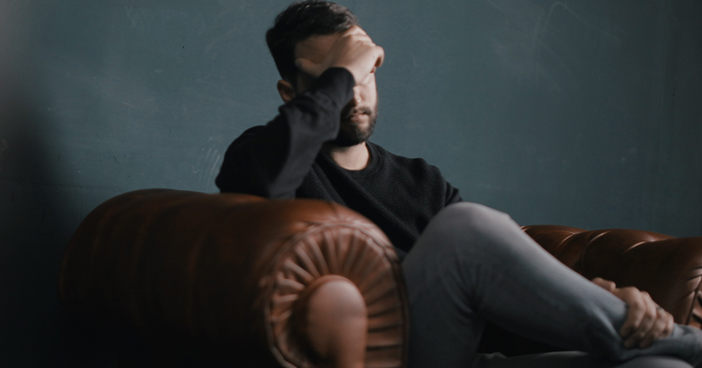 A man on a couch hiding his face
