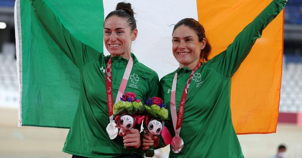 Two women with medals around their necks holding up an Irish flag
