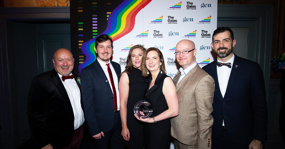 A group of well dressed people holding an award