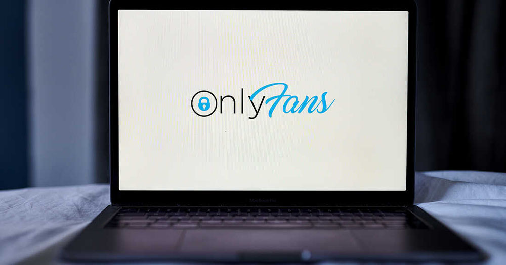 A laptop on a bed with the word OnlyFans on the screen