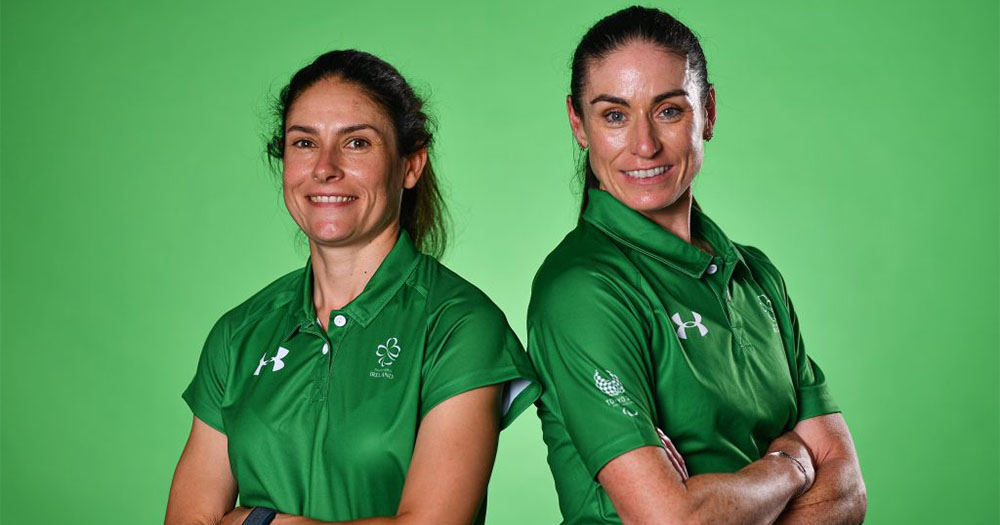 Two women in sporting t-shirts pose back to back
