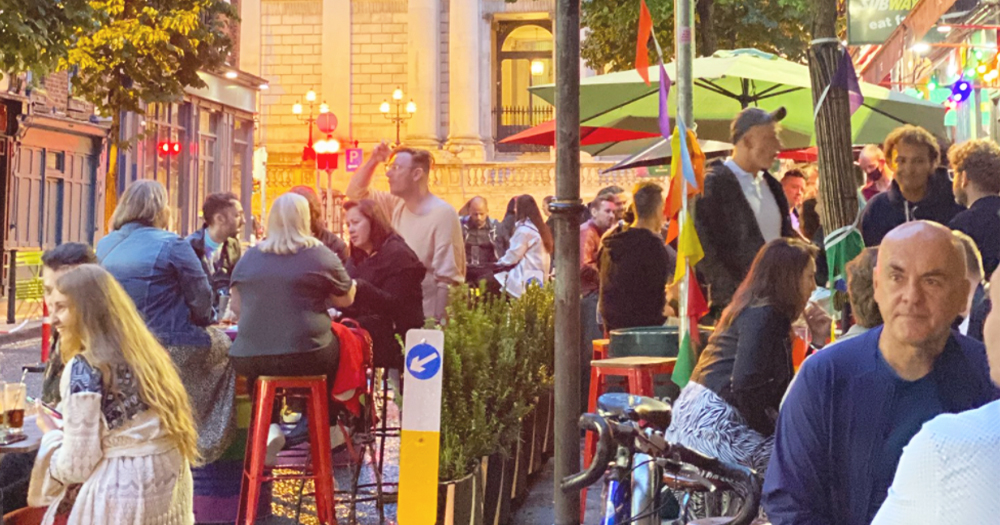 People sitting at tables on the street socialising