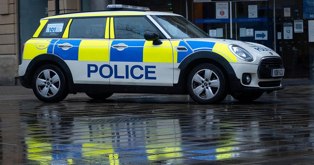 A UK police car on a rainy street