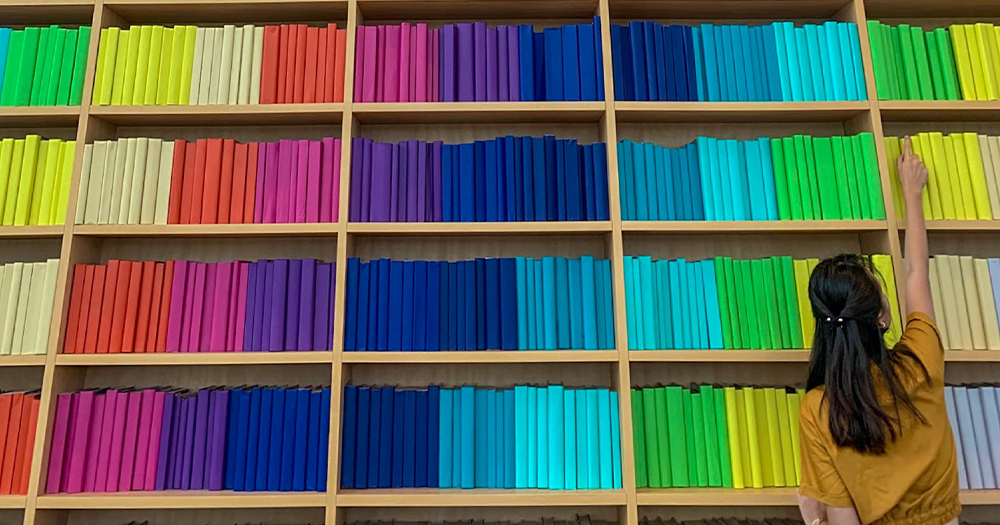 A woman standing in front of shelves filled with rainbow coloured books