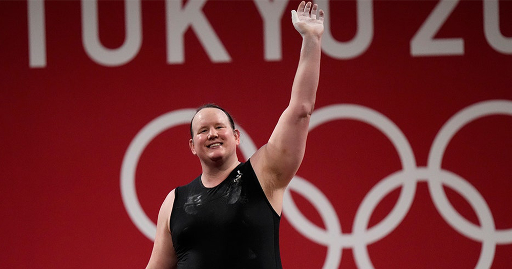 A strong smiling woman at an Olympic event waving to onlookers