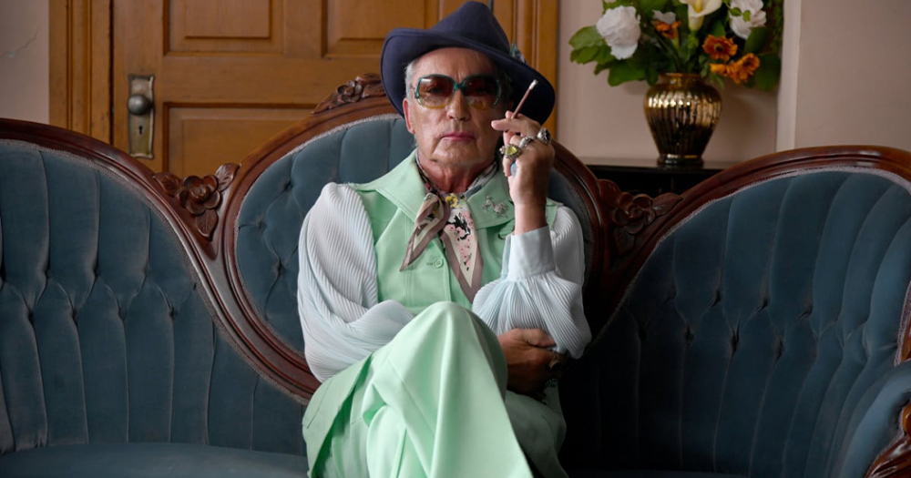 A flamboyantly dressed old man smoking on a couch