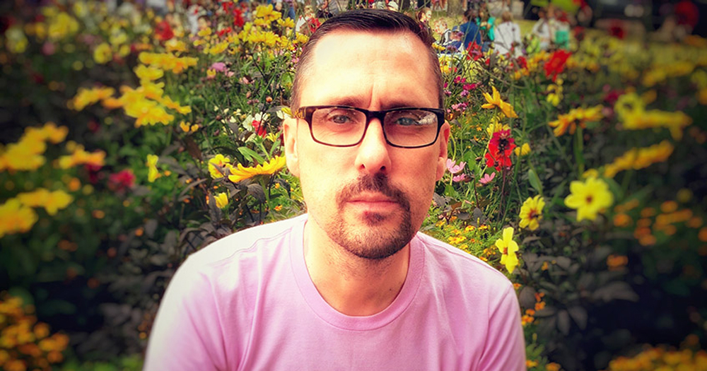 a man wearing glasses and a pink shirt poses in front of a garden in bloom