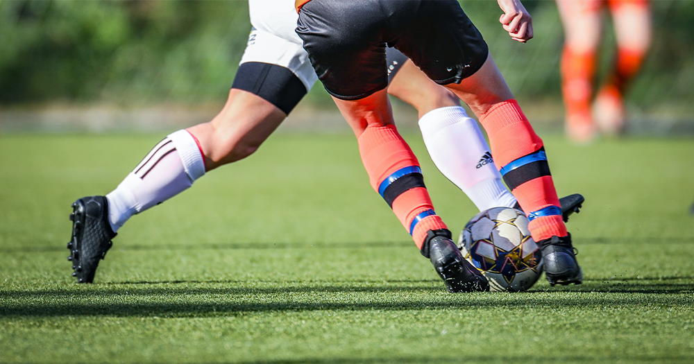 The legs of two footballers involved in a tackle