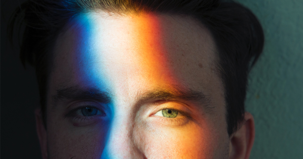 Close up of man's face with rainbow light across his face