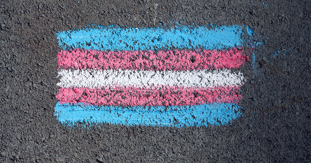 trans flag drawn in chalk on a piece of road to illustrate a piece about UK guidelines about transgender folks in sport