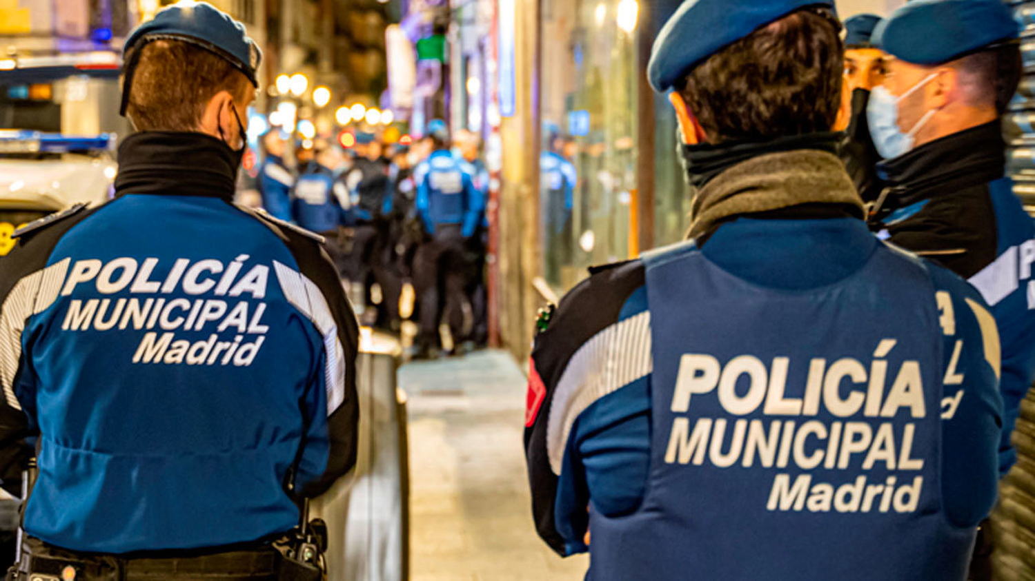 Three Spanish police officers have their backs to the camera. They are standing on a busy street at night time.