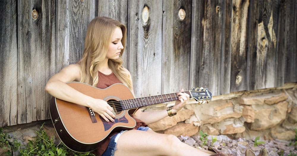 Girl sitting outsite against wooden fence playing an accoustic guitar