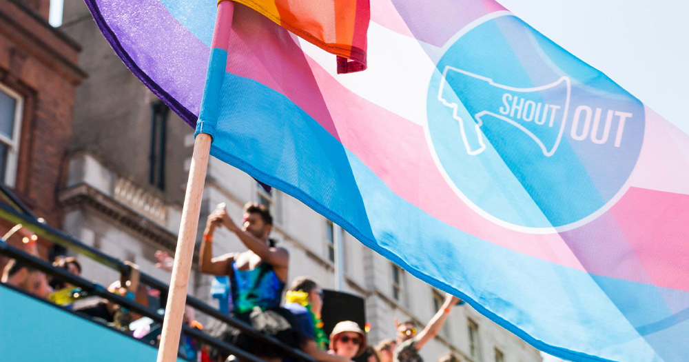 A trans flag in the foreground and a Pride celebration behind