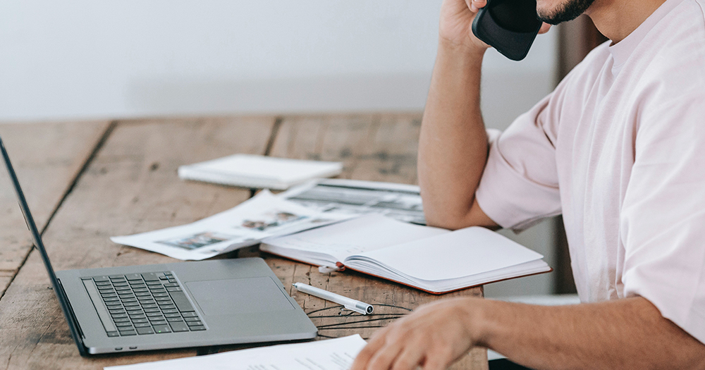 Image of a person sitting at a laptop taking a mobile telephone call to illustrate a recruitment call for National LGBT+ Helpline