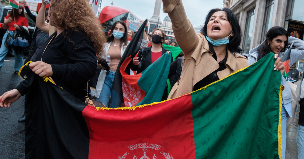 Women at a protest holding the Afghanistan flag. LGBTQ+ Afghans face uncertain future as Taliban announces new government.
