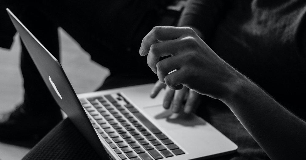 a persons hands on their open laptop