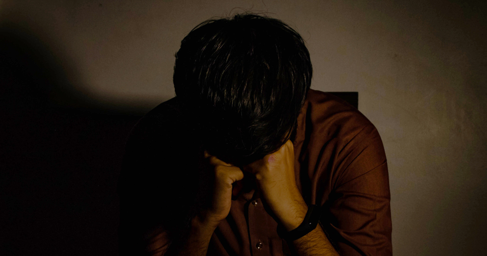 Closeup of a distressed man sitting with his head in his hands in a dimly lit room