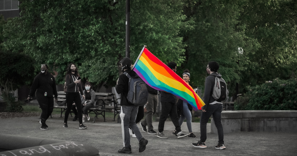 Outdoors, a group of people march, one carrying a rainbow flag