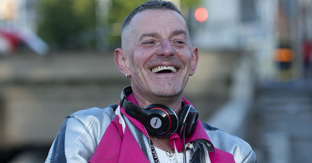 A smiling man on a street with headphones around his neck